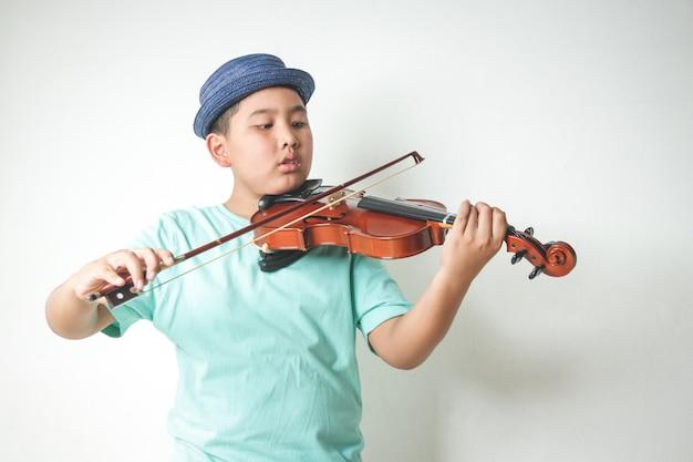 Il ragazzino asiatico che indossa un cappello suona e suona il violino nella stanza bianca.