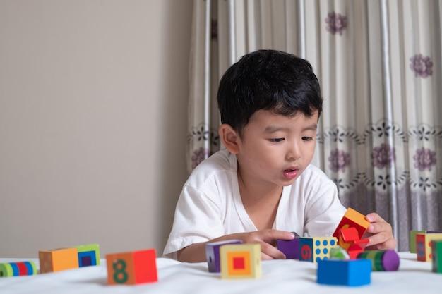 Il ragazzino asiatico sveglio di 3 anni gioca il puzzle del blocco quadrato a casa sul letto