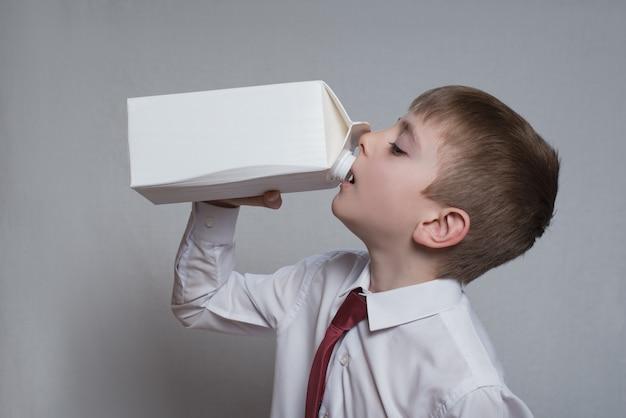 Il ragazzino beve da un grande pacchetto bianco.
