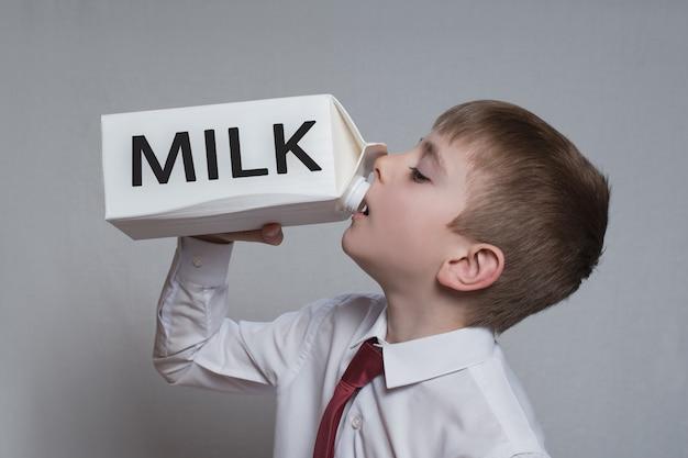 Il ragazzino beve da un grande pacchetto di latte bianco. camicia bianca e cravatta rossa.