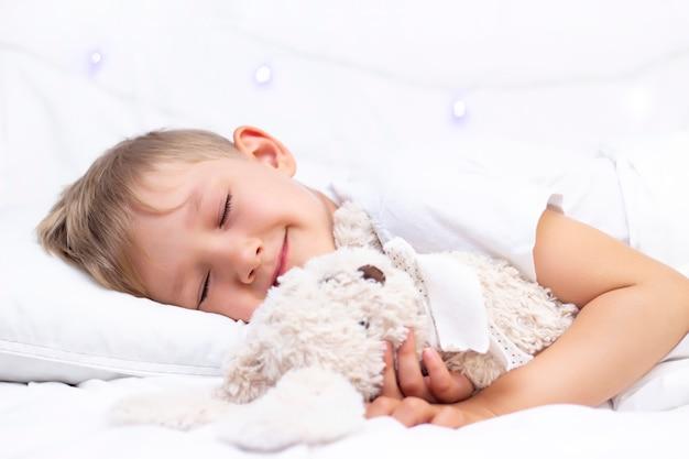 Il ragazzino bianco affascinante dorme a letto. abbraccia un peluche