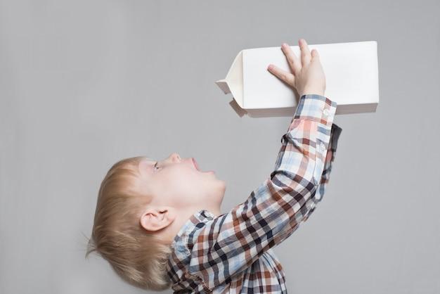 Il ragazzino biondo beve da un grande pacchetto bianco.