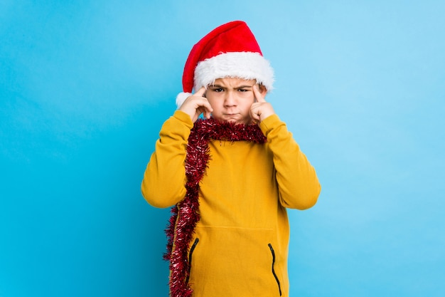 Il ragazzino che celebra il giorno di natale che porta un cappello di santa isolato ha messo a fuoco su un compito, mantenendo gli indici che indicano la testa.