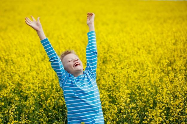 Il ragazzino che salta di gioia su un prato in una giornata di sole