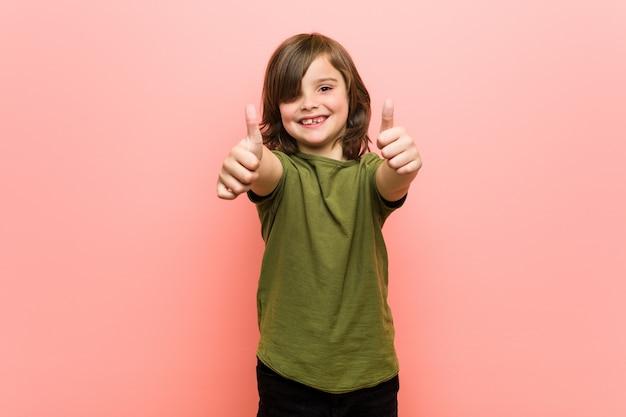 Il ragazzino con i pollici aumenta, incoraggia qualcosa, supporta e rispetta il concetto.