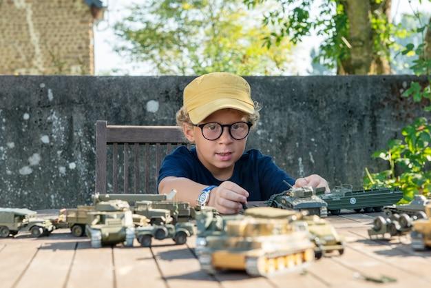 Il ragazzino con una protezione gialla gioca con i giocattoli all'esterno