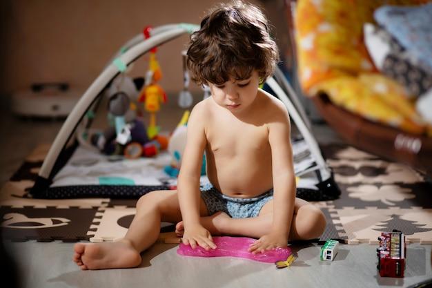 Il ragazzino dai capelli ricci in pantaloncini gioca con la melma nella sua stanza, per non sporcarsi i vestiti.