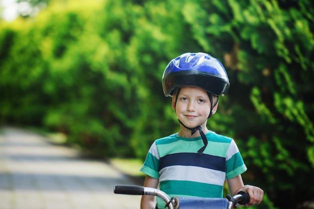 Il ragazzino del ritratto in casco su una bicicletta alla strada asfaltata nel parco dell'estate.