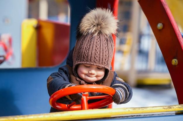 Il ragazzino divertente gioca con un'automobile del giocattolo nel parco
