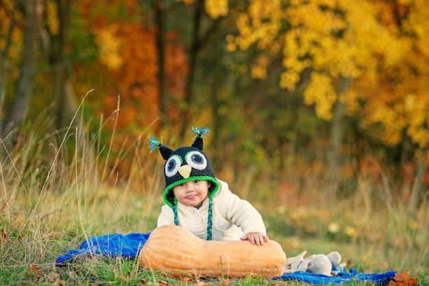 Il ragazzino divertente in un cappuccio tricottato mostra la lingua, sedendosi sull'erba con la zucca e gli alberi di autunno