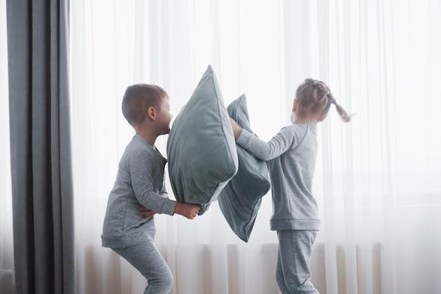 Il ragazzino e la ragazza hanno organizzato una lotta di cuscini sul letto nella camera da letto. i bambini cattivi si battono a vicenda i cuscini. a loro piace quel tipo di gioco