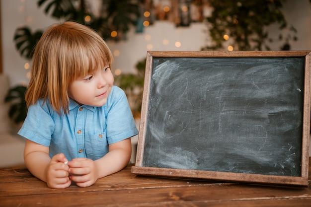 Il ragazzino esamina il tavolo da disegno vuoto