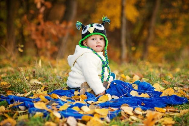 Il ragazzino felice in vestiti caldi mostra una lingua, seduto su un plaid blu e giocando con i giocattoli su un prato verde con foglie di autunno a terra.