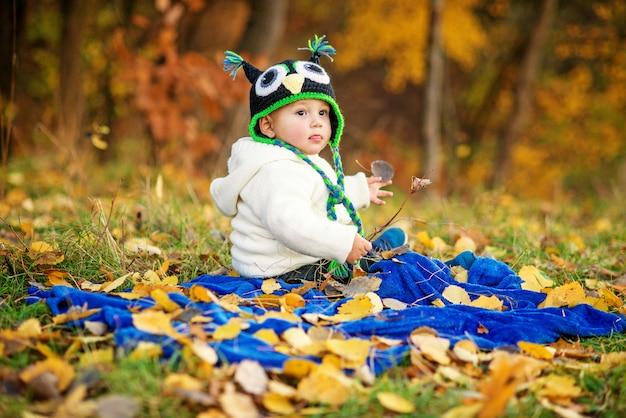 Il ragazzino felice in vestiti caldi mostra una lingua, seduto su un plaid blu e giocando su un prato verde con foglie d'autunno a terra.