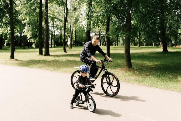 Il ragazzino felice va in bicicletta con un giovane papà nel parco