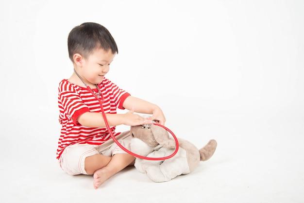 Il ragazzino finge come medico che controlla la bambola del cane
