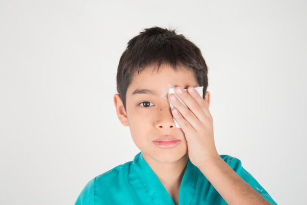 Il ragazzino ha dolore agli occhi usa la benda per coprire