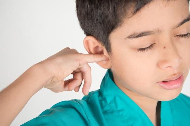 Il ragazzino ha mal di orecchio qualcosa bloccato nell'orecchio