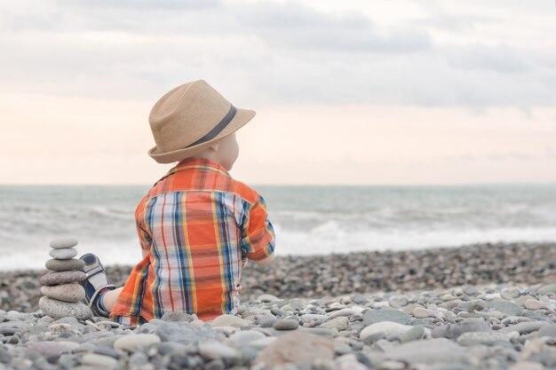 Il ragazzino in cappello si siede su una spiaggia di ciottoli