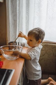 Il ragazzino in cucina aiuta la mamma a cucinare. il bambino è coinvolto nella cottura.