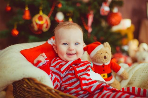 Il ragazzino in pigiami spogliati si siede davanti ad un albero di natale