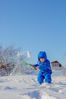 Il ragazzino scava e gioca nella neve invernale, attività invernali per bambini.