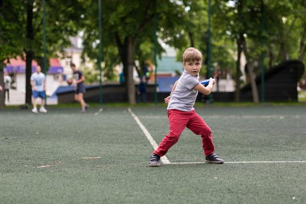 Il ragazzino sta giocando a frisbee