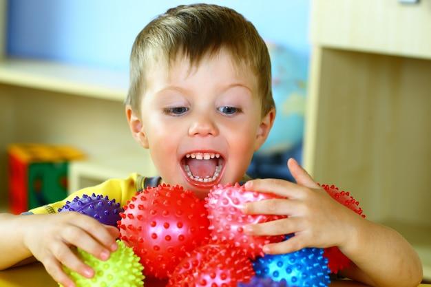 Il ragazzino sta giocando con le palle colorate