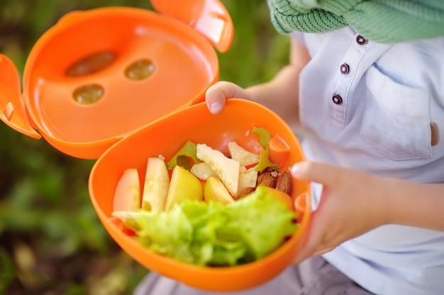 Il ragazzino sta mangiando il suo pranzo sull'erba nel parco in estate.