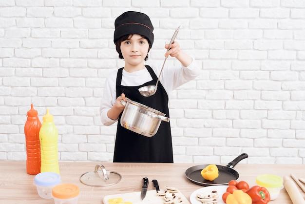 Il ragazzino sta padroneggiando la professione di cuoco.