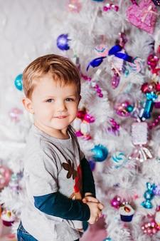 Il ragazzino sta prima di un albero di natale bianco