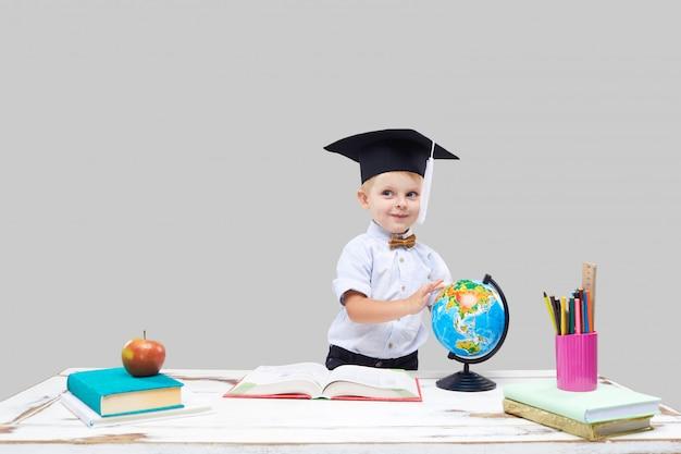 Il ragazzino sta studiando mentre indossa un cappello di laurea su una parete isolata grigia
