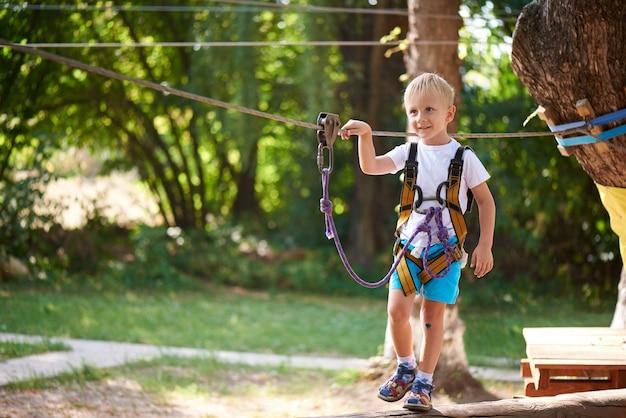 Il ragazzino supera l'ostacolo nel parco della corda.