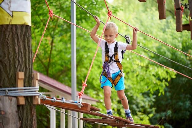 Il ragazzino supera un ostacolo in un parco di divertimenti