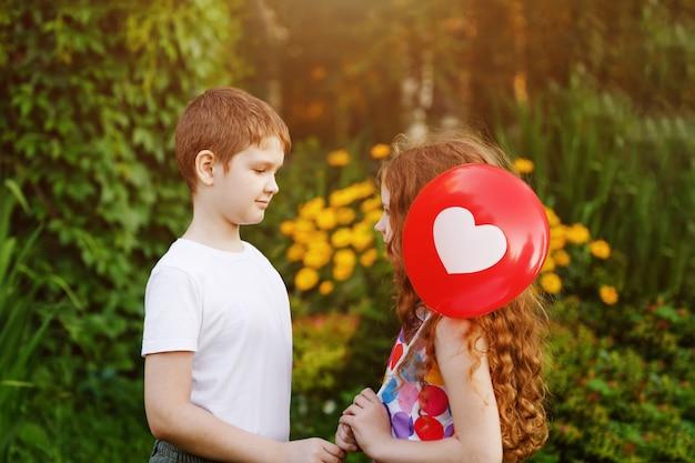 Il ragazzino sveglio con il regalo rosso balloons la sua ragazza dell'amico.