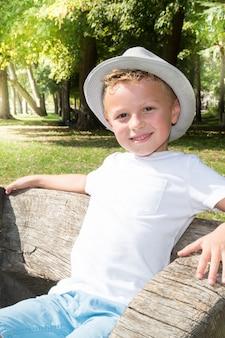 Il ragazzino sveglio davanti ad un prato si siede sul banco con il cappello