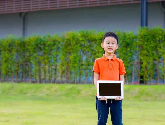 Il ragazzino sveglio è passeggiata e tenendo la compressa in mani nel parco