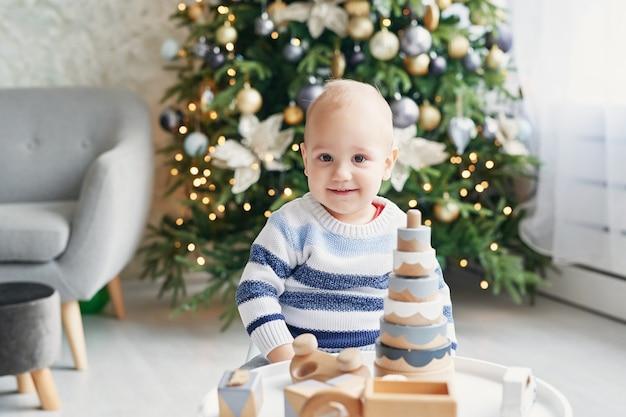 Il ragazzino sveglio sta giocando con il treno di legno del giocattolo, l'automobile del giocattolo, la piramide ed i cubi, imparanti il concetto di sviluppo. sviluppo delle capacità motorie, dell'immaginazione e del pensiero logico dei bambini