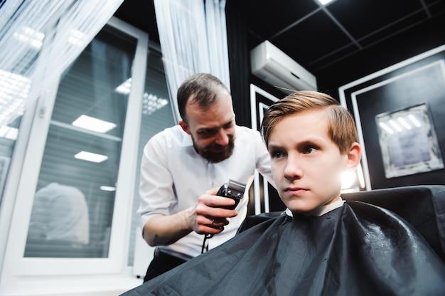 Il ragazzino sveglio sta ottenendo il taglio di capelli dal parrucchiere dal barbiere.