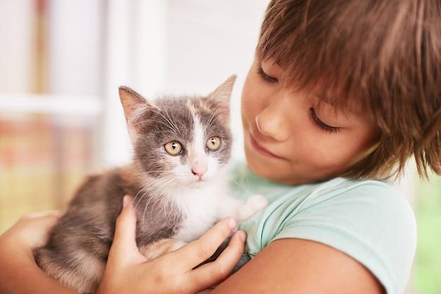 Il ragazzino tiene il gattino in bianco e nero sulla sua spalla