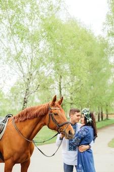 Il ragazzo abbraccia sensibilmente la sua bella ragazza e tiene un cavallo per una briglia sullo sfondo degli alberi