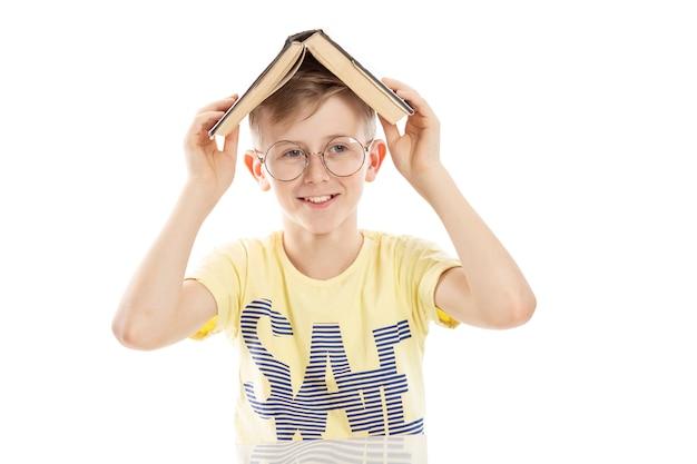 Il ragazzo adolescente con gli occhiali con un libro in testa sta ridendo. si siede vicino al tavolo. isolato su sfondo bianco.