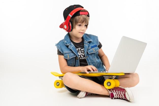Il ragazzo adolescente si siede sul pavimento in giacca di jeans e pantaloncini. scarpe da ginnastica con penny giallo, auricolari rossi e laptop isolato