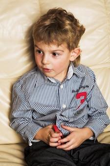 Il ragazzo adorabile si siede sul sofà