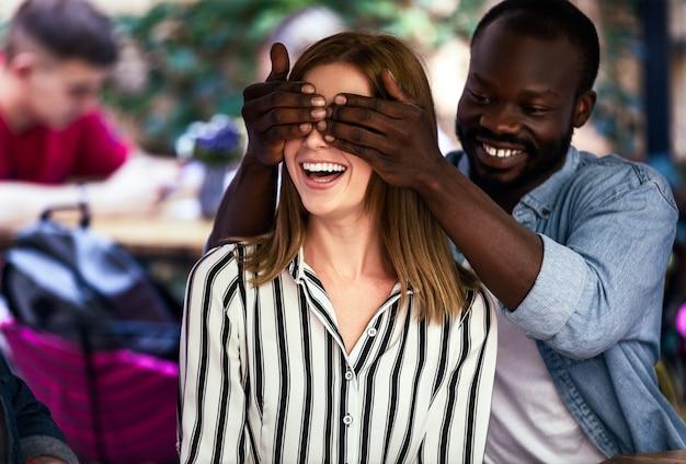 Il ragazzo africano sta chiudendo gli occhi con le mani di una ragazza caucasica
