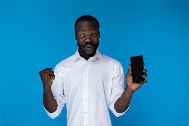 Il ragazzo afroamericano barbuto emozionante sta mostrando il telefono cellulare