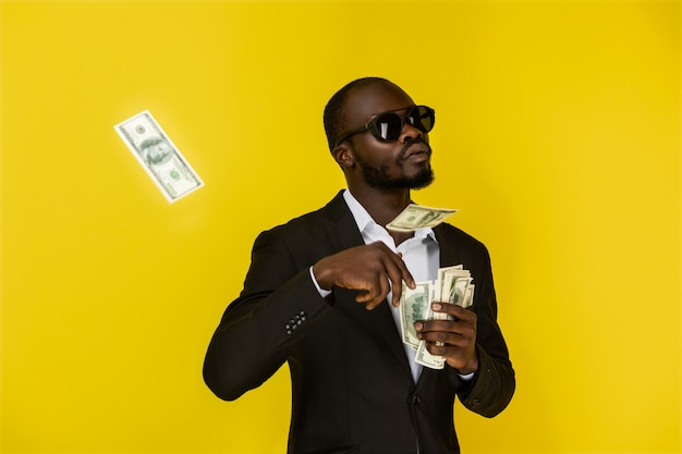 Il ragazzo afroamericano barbuto sta gettando dollari da una mano, indossando occhiali da sole e abito nero