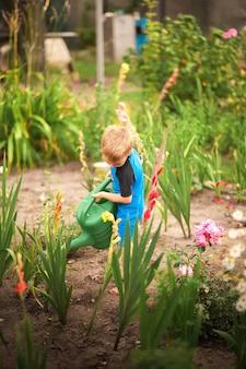 Il ragazzo aiuta con il giardino estivo. giochi per bambini con acqua nel cortile.