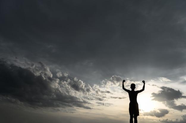 Il ragazzo alzò la mano nel cielo per chiedere pioggia durante il tramonto.