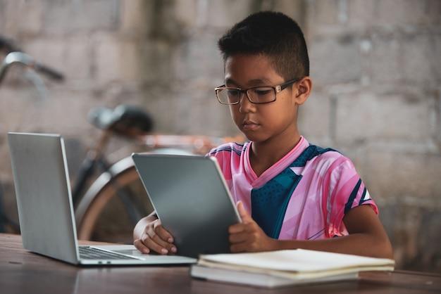 Il ragazzo asiatico che per mezzo del computer portatile sulla tabella, ritorna allo shcool